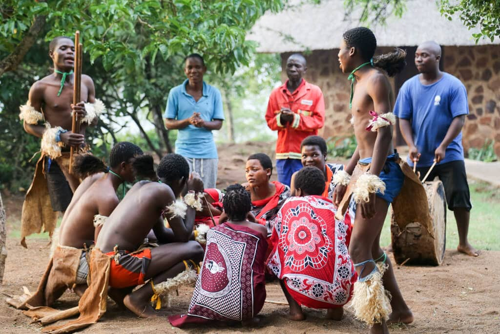 A group of tribal dancers huddle in a circle