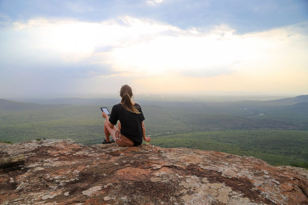 A woman in a black t-shirt sits on a cliff's edge at sunset