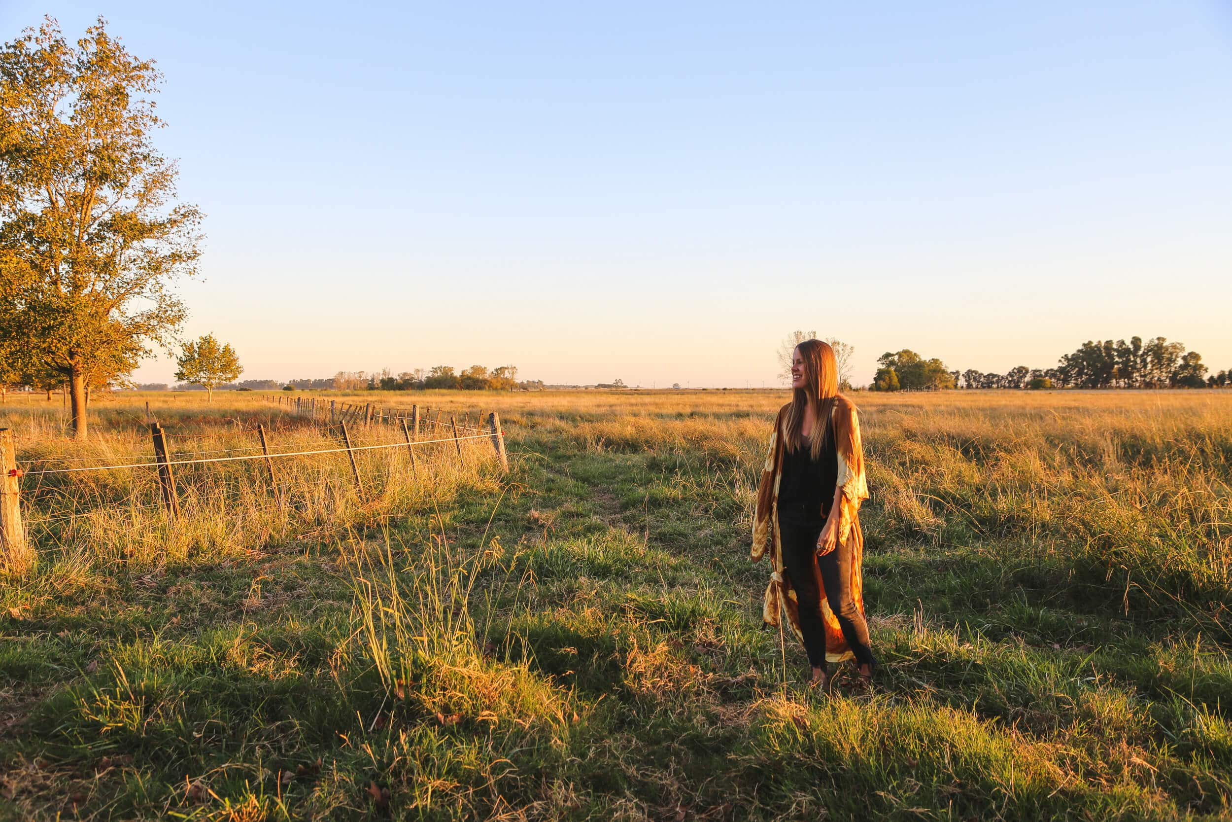 A woman stands in a pasture at sunset