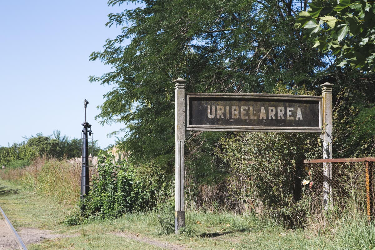 An aged city sign in the grass next to train tracks