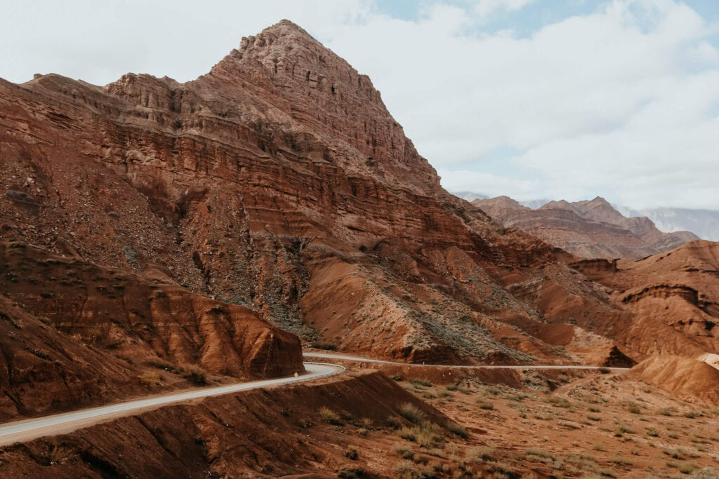 A highway weaves along next to a red mountain in the desert