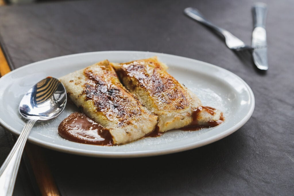 Two crepes ooze dulce de leche onto a plate next to a large silver spoon