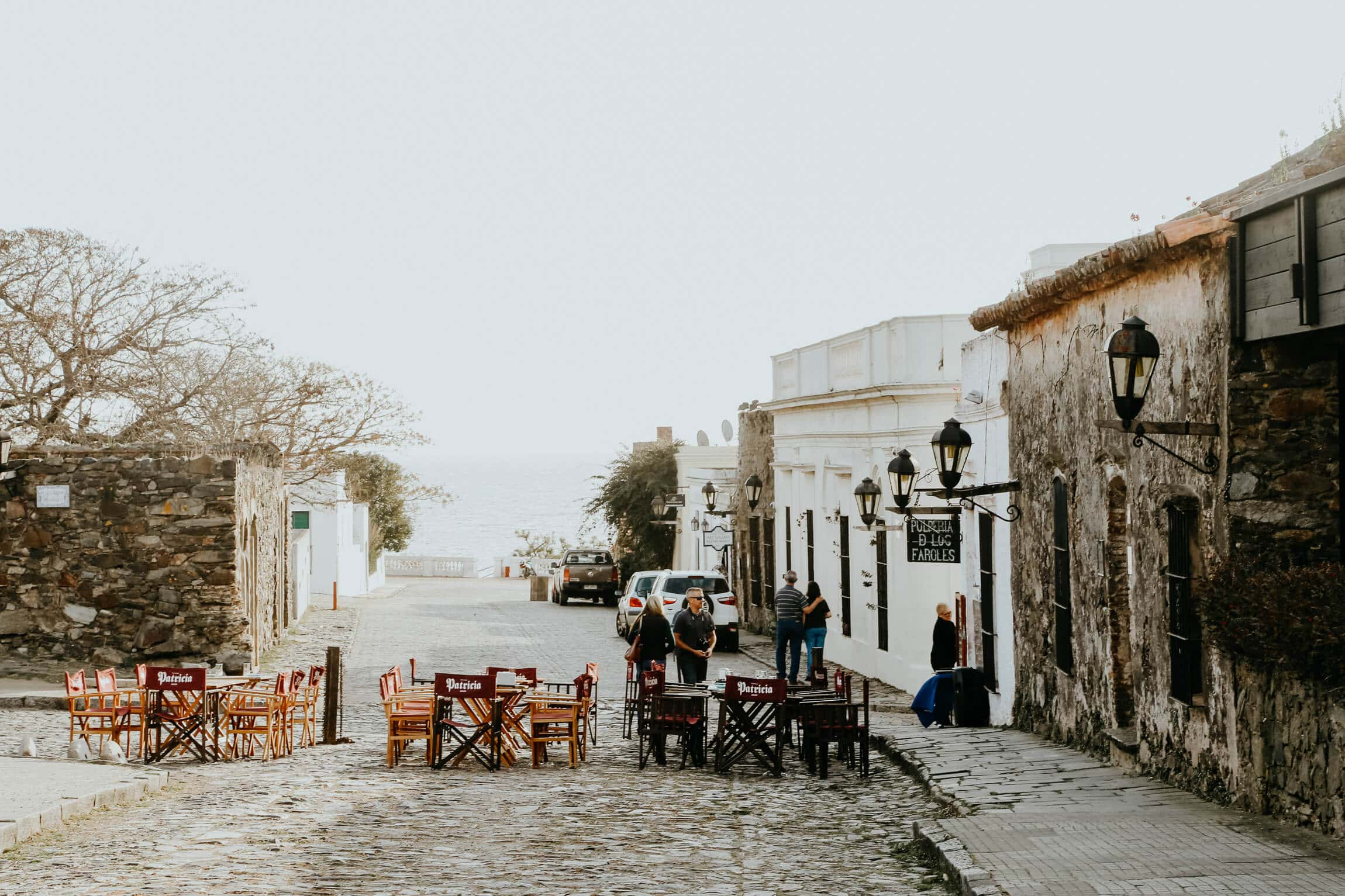 Tables and chairs on a cobblestone street by colonial buildings