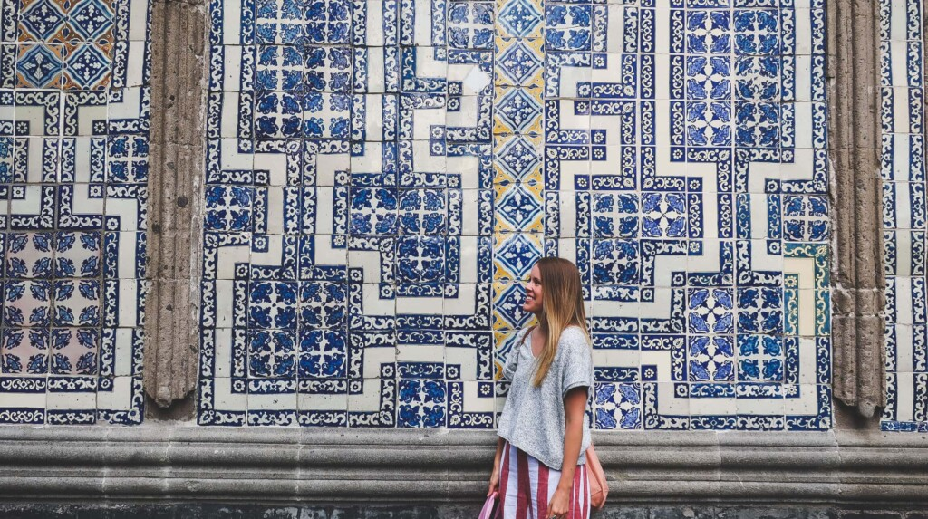 A woman in a grey sweater stands in front of a blue and white tiled wall