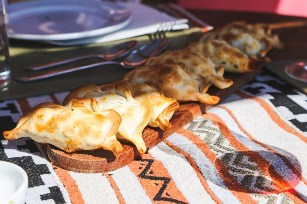 A wooden tray of empanadas on a woven tablecloth