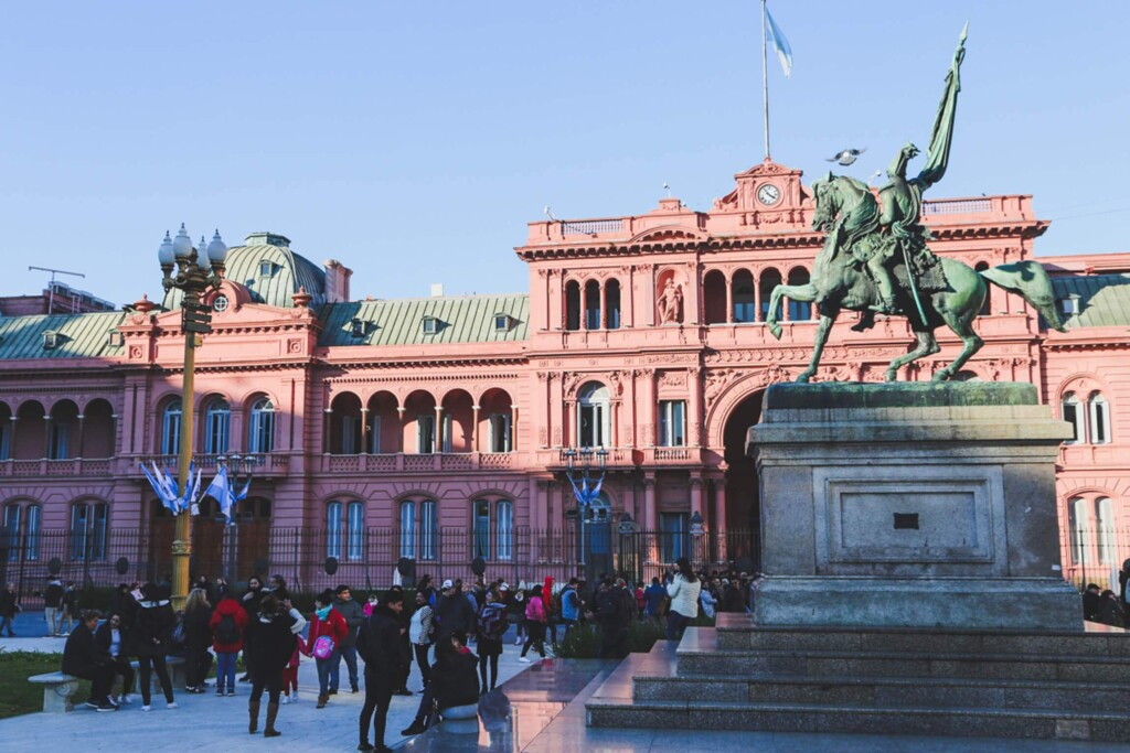 A statue of a man on a horse on a pedestal in front of La Casa Rosada government building