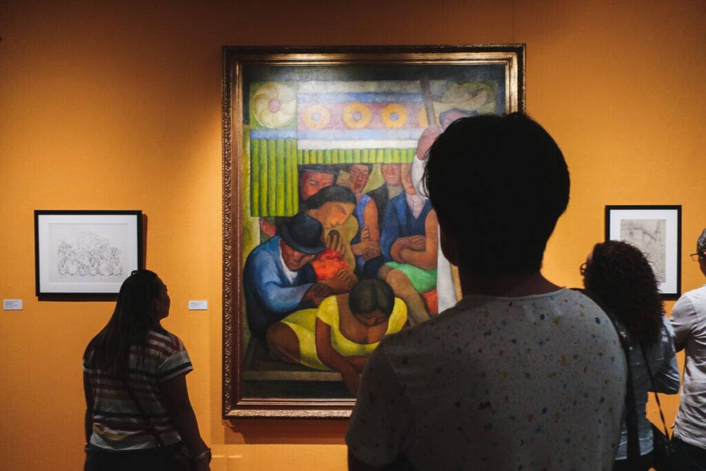 Three people stand in front of a painting on an orange wall in a museum