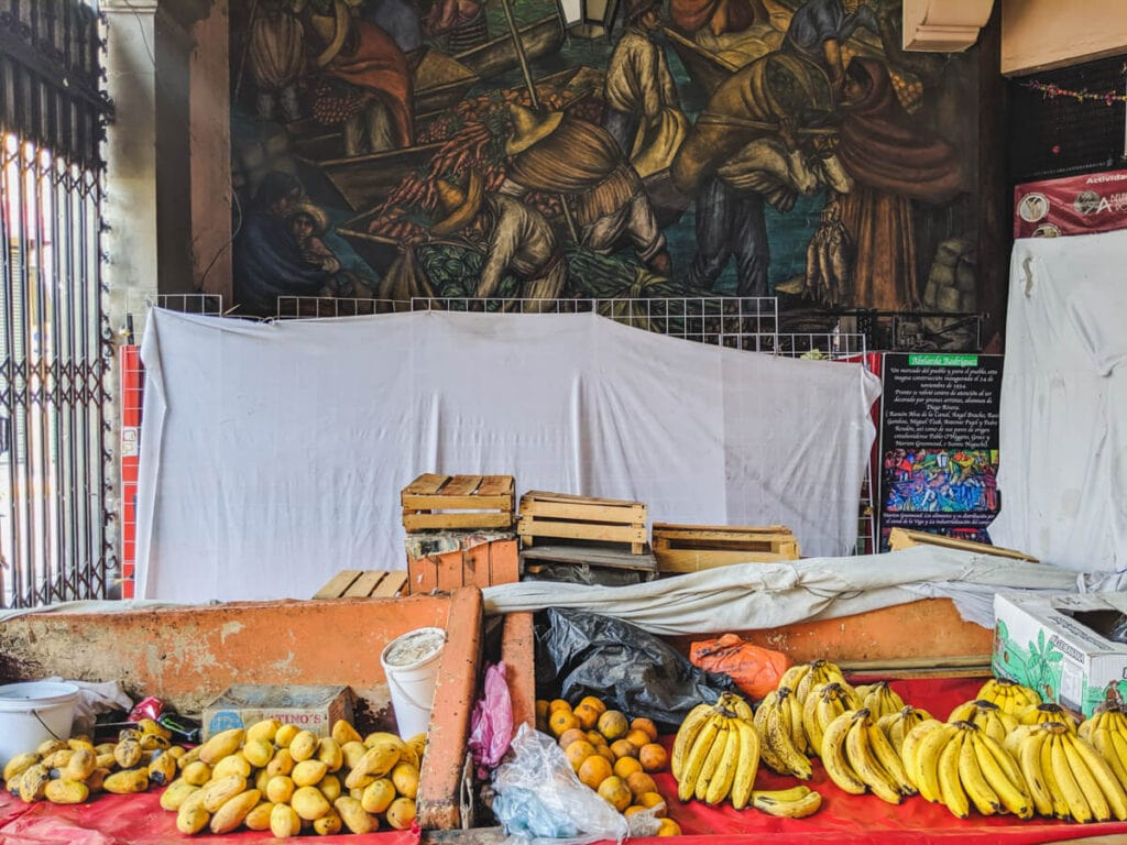 A mural on the wall of a market with bananas and mangos on the market table