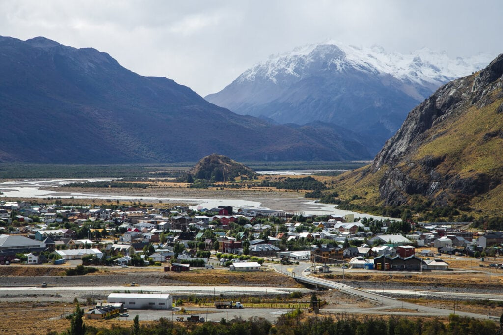 A village in the valley surrounded by snowy mountains