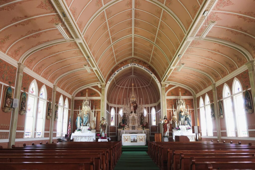 Wooden pews inside a pale pink church